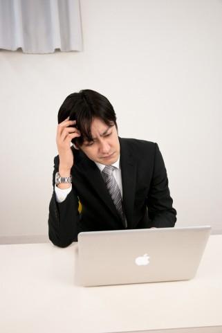 PC前で悩んでるビジネスマン